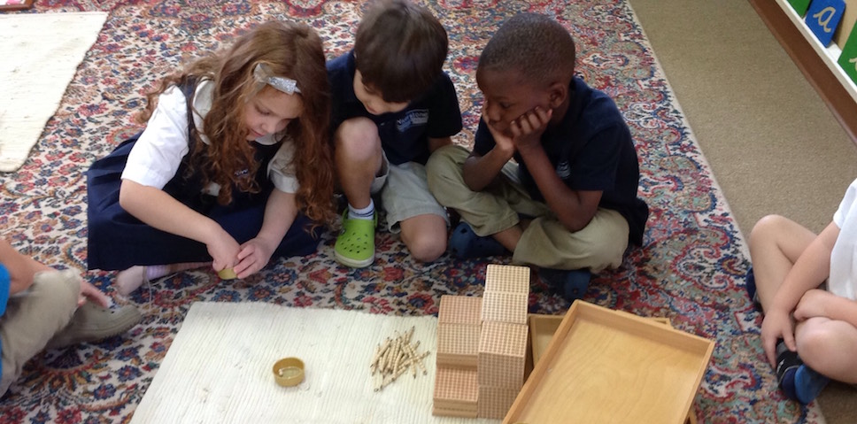 Primary students working with Golden Beads material